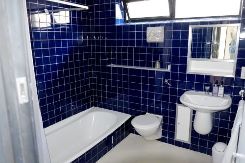Main bathroom with bath tub and over bath shower