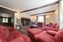 Large lounge with comfy sofas and original inglenook fireplace complete with logburner