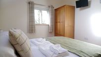 The Hayloft - main bedroom with fluffy towels and space for a cot