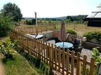 The terrace looks out over open farmland. It is fenced with a gate for children and dog stays in mind.
