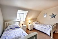 Twin room with comfortable beds, dormer windows and a sink