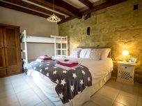 Family room with king size bed and bunks in Drake Cottage