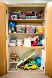 The stocked games/baby equipment cupboard