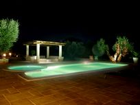 Pool by night with outside sofas