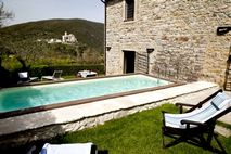 Swimming pool, gardens and view to Antognolla Castle