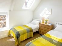 The sunny twin bedroom also has room for a cot