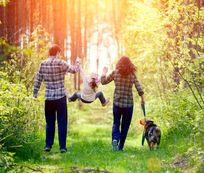 Family In Woods Walking Dog