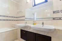 Bathroom with shower over bath and double basins