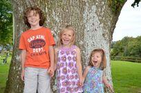 Siblings having fun by the old oak tree