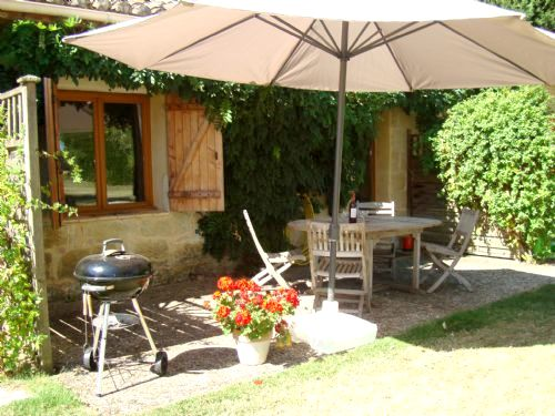 Drake cottage terrace overlooking the gardens with views towards the pool and the fields beyond