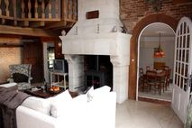 Spacious lounge with woodburning stove, leading to dining room
