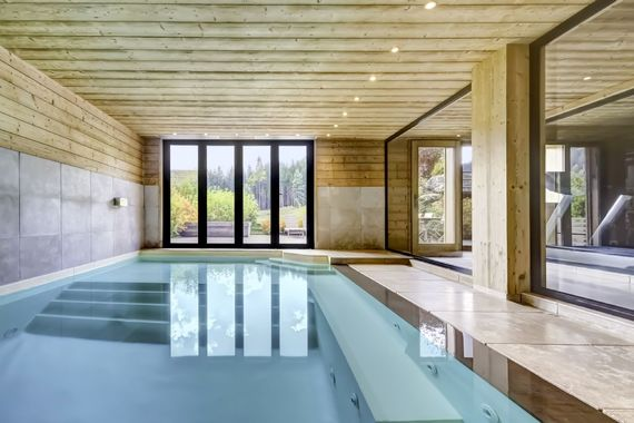 Indoor heated pool with Endless jet and sliding doors opening onto a communal deck