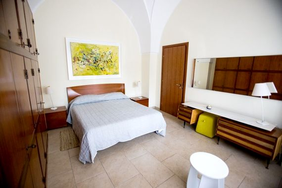 Master bedroom in original room with a mix of retro and modern furniture as well as local artwork.