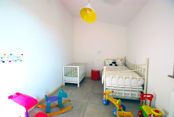 THE KIDS BEDROOM WITH A COT AND SINGLE BED