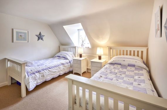 This bedroom also has two comfortable single beds, dormer windows a sink