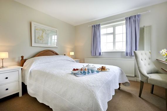 Main bedroom with double bed, dressing table and views down to the water