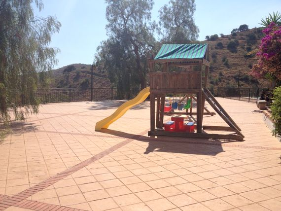 large communal terrace with climbing frame and toys for young children