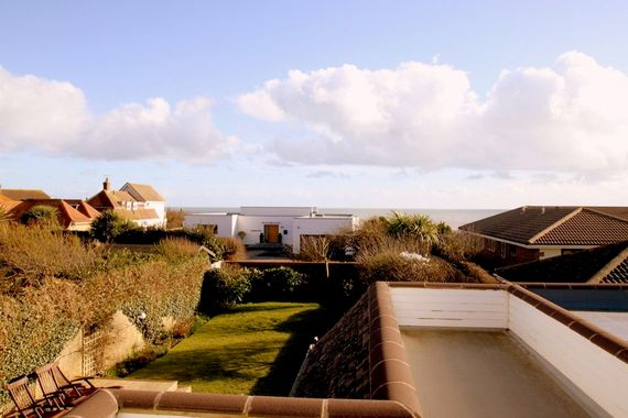 View over balcony and rear garden to the sea