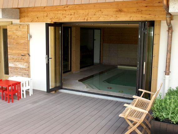 Sliding folding doors open onto a large communal deck