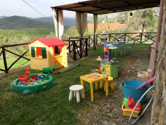 Playarea with playhouse, sandpit, play kitchen, table and stools and other toys.