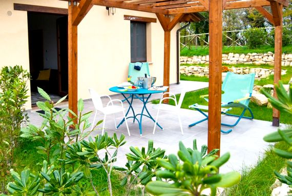The Pinolo terrace with loungers, table and chairs, shade & a gas BBQ