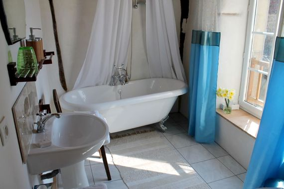 Spacious bathroom with claw foot bath looking onto the beautiful old church